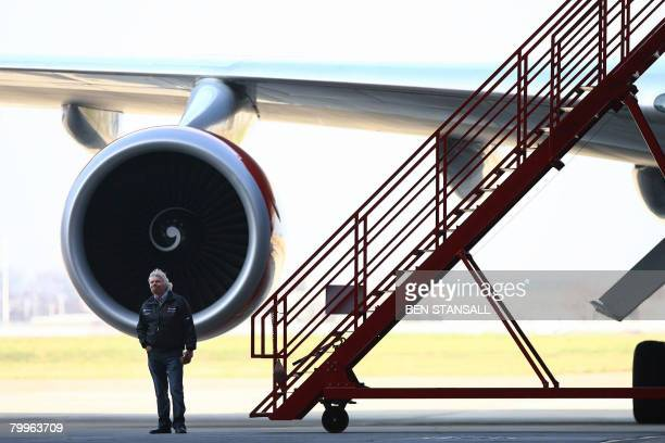 Richard Branson poses in front of a Virgin Atlantic Boeing 747 before it embarks on the first test flight using biofuel made from coconut oil at...