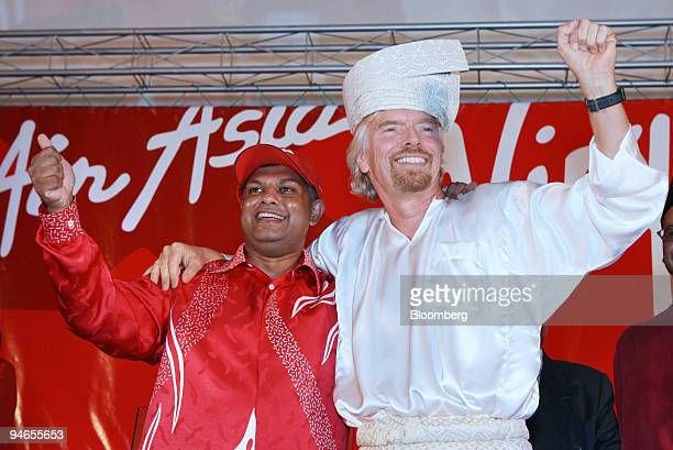 Richard Branson right chairman of Virgin Group Ltd donning a malaywarrior headgear poses with Tony Fernandes chief executive officer of AirAsia at a...