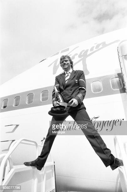 Richard Branson seen here dressed as a Virgin Atlantic pilots with a bottle of champagne posing for the press in front of Virgin Atlantic's first...