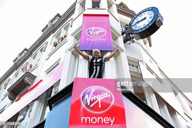 Richard Branson the founder of Virgin Group Ltd center gestures from the window of Virgin Money's first high street bank while dressed in a Newcastle...