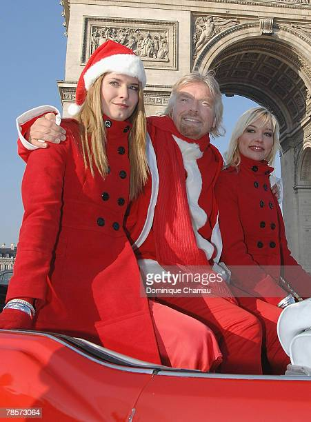Richard Branson , wearing a Santa suit, travels in a sports car along the Champs-Elysees Avenue, passing the landmark Arc de Triomphe, on December...