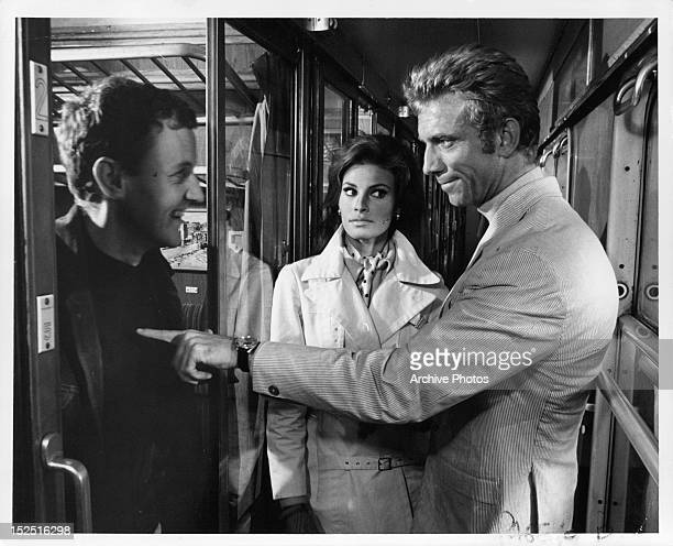 Richard Briers smiling as Anthony Franciosa points to him and Raquel Welch watches in a scene from the film 'Fathom' 1967