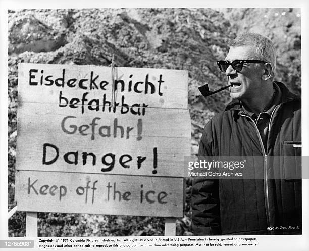 Richard Brooks writerdirector of the film surveys sign leading to a frozen lake in Lilleyhammer Norway for the film '$' 1971