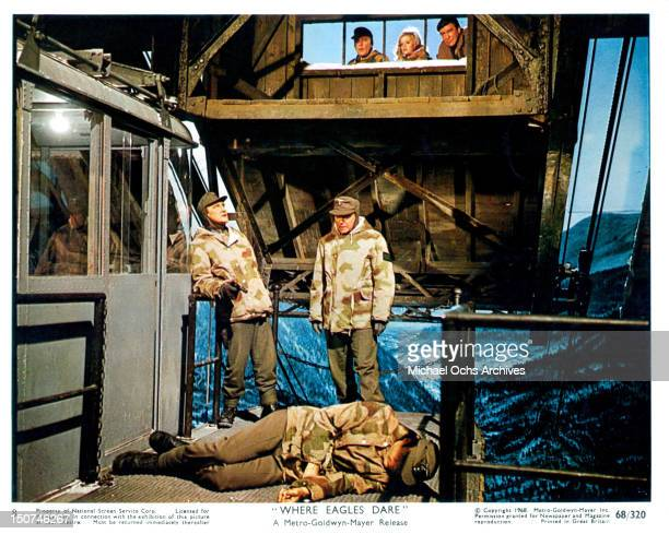 Richard Burton and Mary Ure looking down through a window observing the men below in military uniforms in a scene from the film 'Where Eagles Dare',...