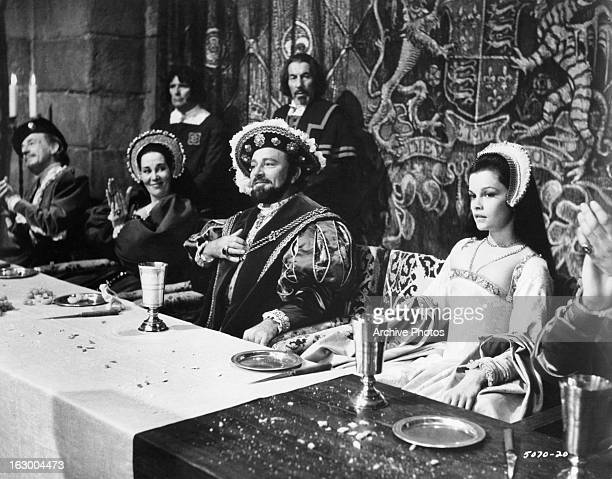 Richard Burton sits at a table with Geneviève Bujold in a scene from the film 'Anne Of The Thousand Days' 1969