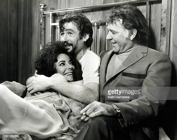 Richard Burton surprises costars Elizabeth Taylor and Peter O'Toole by joining them in bed for a photo opportunity during the filming of a love scene...