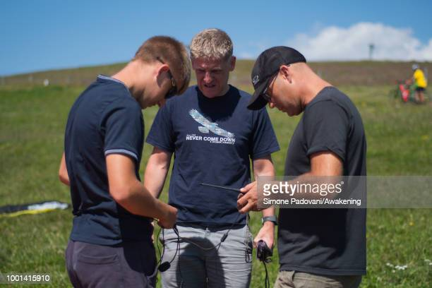 Richard Butterworth checks the settings of the GPS devices with his son and another paraglider before the training on July 18 2018 in Feltre Italy...
