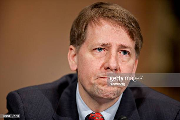 Richard Cordray director of the Consumer Financial Protection Bureau pauses while speaking at a Senate Banking Committee hearing in Washington DC US...