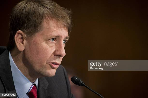 Richard Cordray director of the Consumer Financial Protection Bureau testifies before the Senate Committee on Banking Housing and Urban Affairs with...