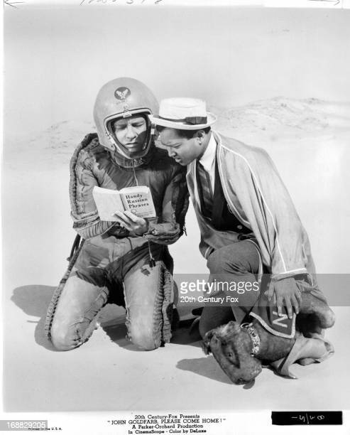 Richard Crenna reads a book held by a man in a space suit in a scene from the film 'John Goldfarb Please Come Home' 1965