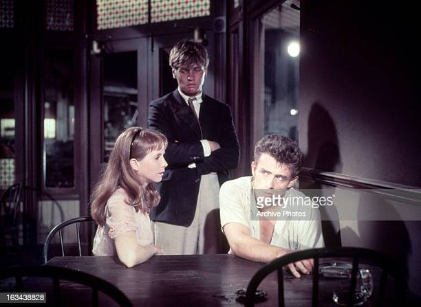 Richard Davalos standing behind a sitting Julie Harris and James Dean in a scene from the film 'East Of Eden' 1955