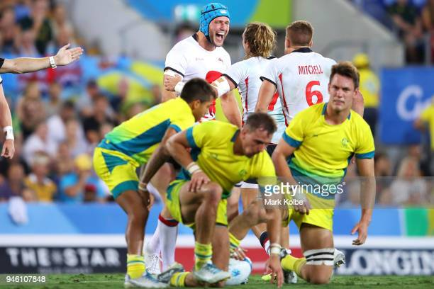 Richard de Carpentier of England celebrates victory as Australia look dejected after defeat during the Rugby Sevens match between Australia and...