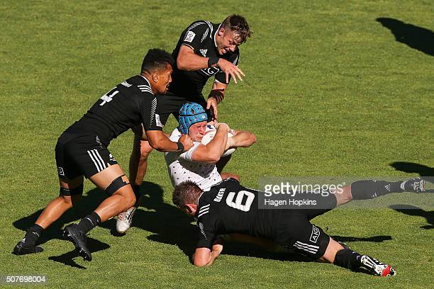 Richard de Carpentier of England is tackled by Ardie Savea Kurt Baker and Tim Mikkelson of New Zealand during the 2016 Wellington Sevens cup...