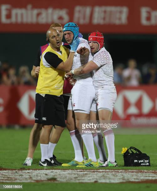 Richard de Carpentier of England receives medical attention and support from team-mate Phil Burgess after sustaining a neck injury during the match...