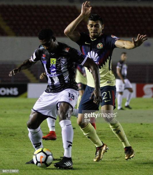Richard Dixon of Panama's team Tauro vies for the ball with Henry Martin of Mexico's America during their second leg match of the Concacaf Champions...