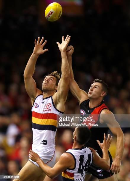 Richard Douglas of the Crows and Conor McKenna of the Bombers compete for the ball during the 2018 AFL round 01 match between the Essendon Bombers...