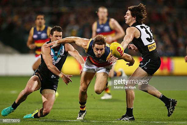 Richard Douglas of the Crows competes for the ball with Travis Boak and Darcy ByrneJones of the Power during the round 22 AFL match between the Port...