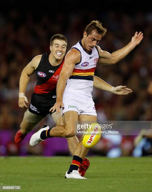 Richard Douglas of the Crows is chased by Zach Merrett of the Bombers during the 2018 AFL round 01 match between the Essendon Bombers and the...