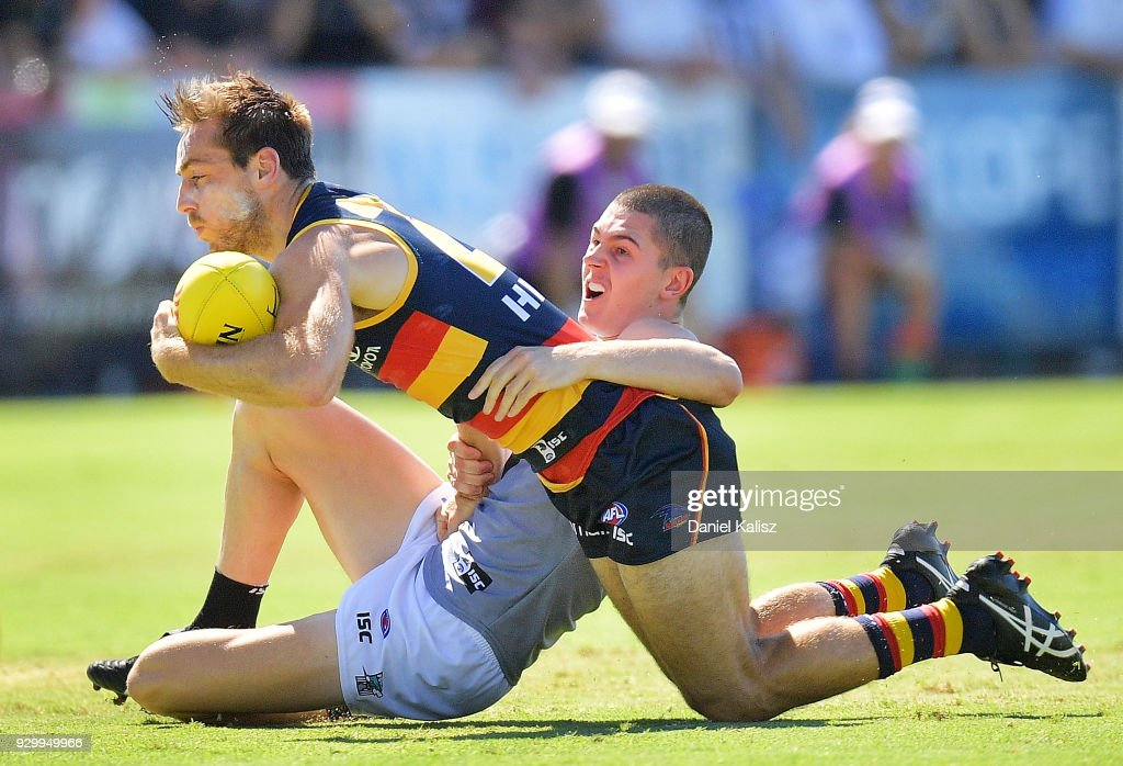 Richard Douglas of the Crows is tackled by Darcy Byrne-Jones of the Power during the JLT Community Series AFL match between Port Adelaide Power and the Adelaide Crows at Alberton Oval on March 10, 2018 in Adelaide, Australia.
