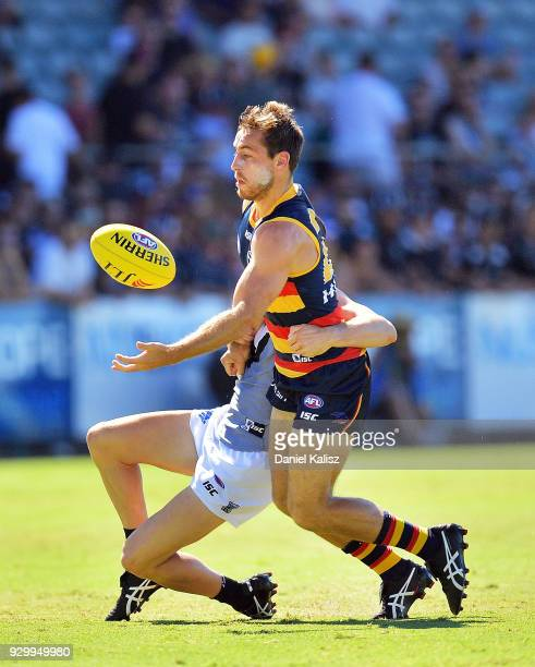 Richard Douglas of the Crows is tackled by Darcy ByrneJones of the Power during the JLT Community Series AFL match between Port Adelaide Power and...