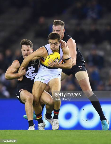Richard Douglas of the Crows is tackled by Matthew Wright and Ciaran Byrne of the Blues during the round 23 AFL match between the Carlton Blues and...
