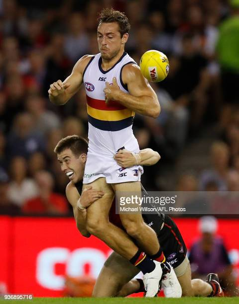 Richard Douglas of the Crows is tackled by Zach Merrett of the Bombers during the 2018 AFL round 01 match between the Essendon Bombers and the...