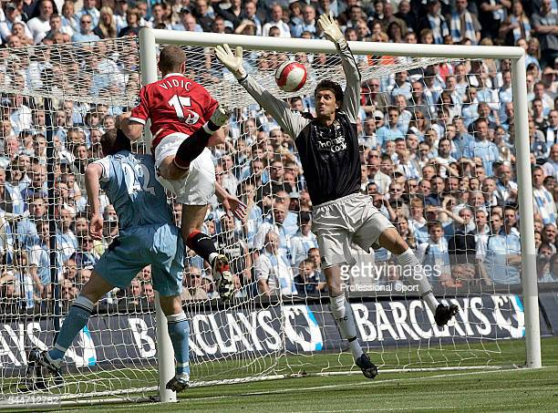 Richard Dunne and goalkeeper Andreas Isaksson of Manchester City and Nemanja Vidic of Manchester United in action during the FA Premier League match...