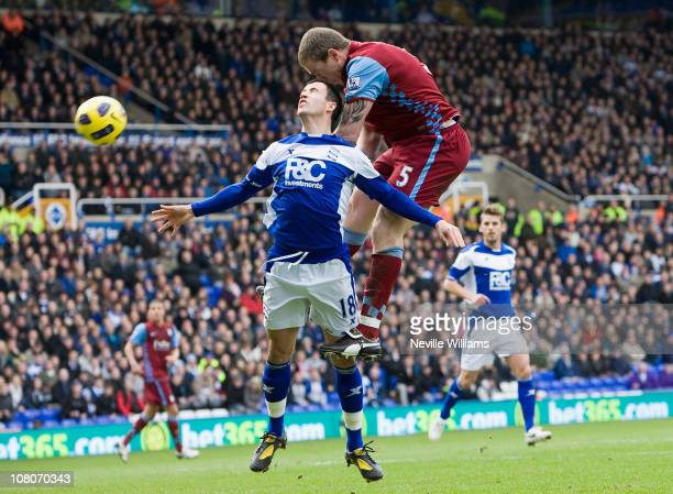 Richard Dunne of Aston Villa heads towards goal with Keith Fahey of Birmingham City challenging on January 16 2011 in Birmingham England