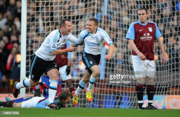 Richard Dunne of Aston Villa looks dejected as Craig Bellamy of Liverpool celebrates scoring to make it 10 with Charlie Adam during the Barclays...