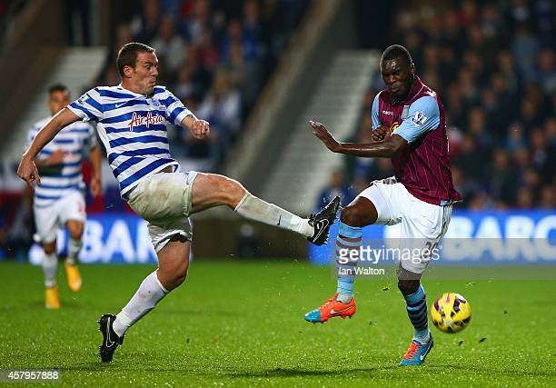 Richard Dunne of QPR is challenged by Christian Benteke of Aston Villa during the Barclays Premier League match between Queens Park Rangers and Aston...