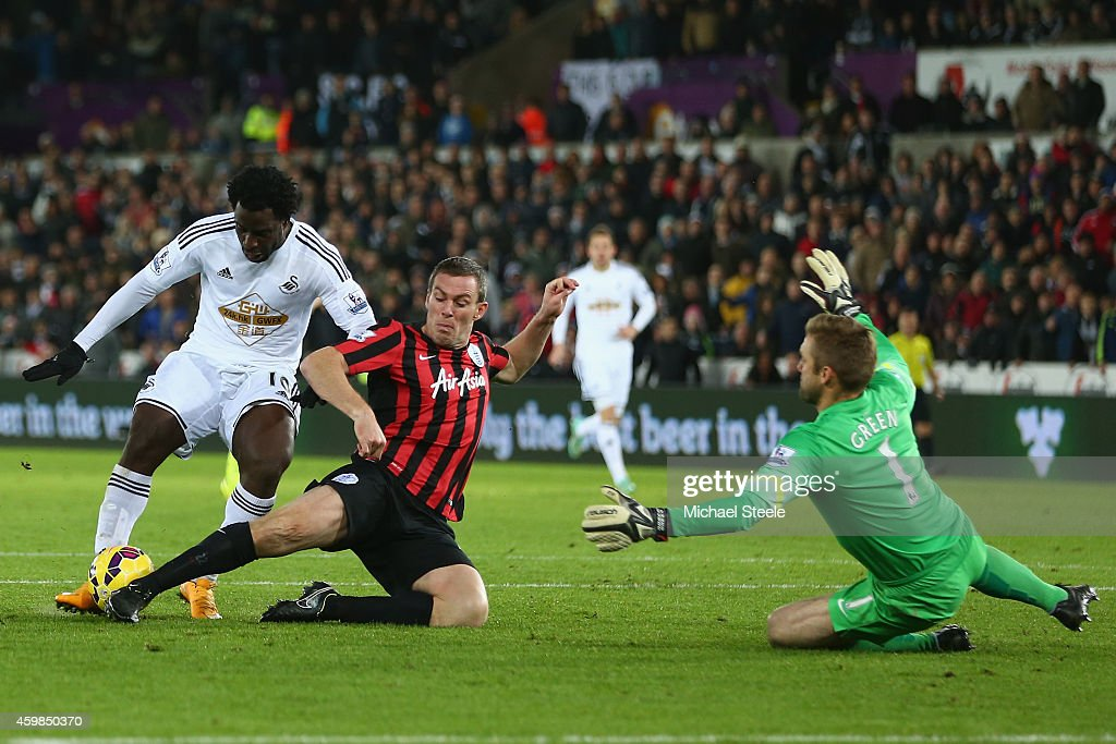 Richard Dunne (C) of QPR tackles Wilfried Bony of Swansea City as goalkeeper Robert Green closes the angles during the Barclays Premier League match at the Liberty Stadium on December 2, 2014 in Swansea, Wales.