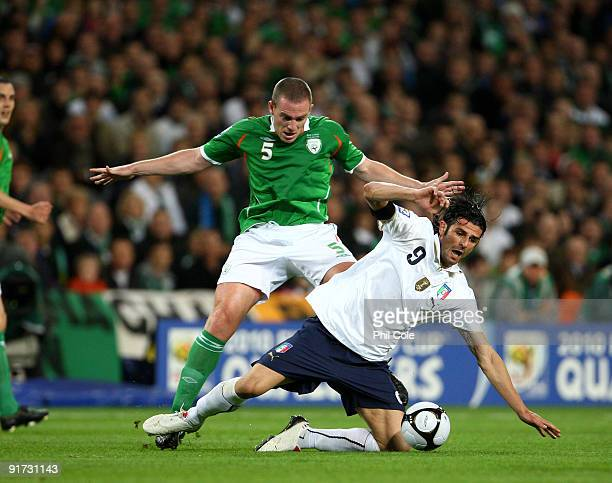 Richard Dunne of Republic of Ireland tackles Vincenzo Iaquinta of Italy during the FIFA 2010 World Cup European Qualifying match between the Republic...