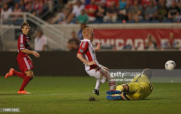 Richard Eckersley of Toronto FC clears a shot by Chris Rolfe of the Chicago Fire past Milos Kocic during an MLS match at Toyota Park on August 4 2012...