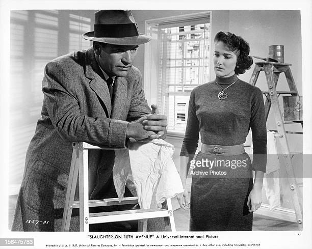 Richard Egan contemplates as Julie Adams watches him in a scene from the film 'Slaughter On Tenth Avenue' 1957