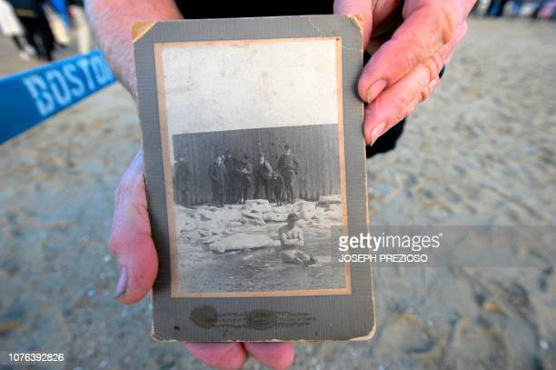 Richard Evans shows off a photo of his grandfather Richard Bolland sitting on ice at the L Street Brownies swim of 1904 during the annual L Street...