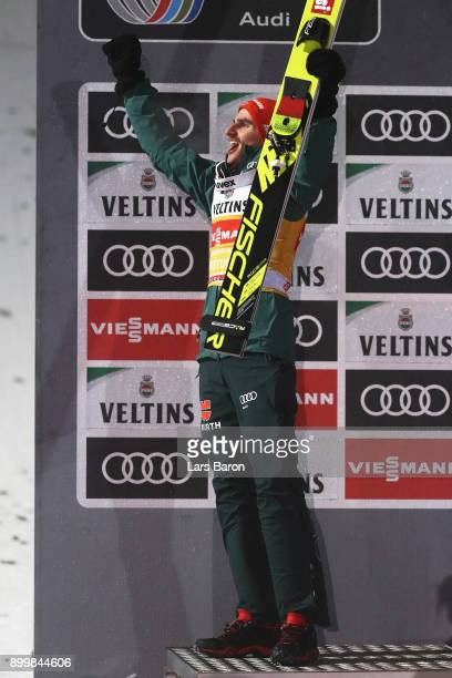 Richard Freitag of Germany celebrates his second place on the podium after the FIS Nordic World Cup on day 2 of the Four Hills Tournament ski jumping...