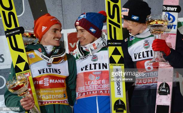Richard Freitag of Germany Kamil Stoch of Poland and Dawid Kubacki of Poland celebrate after the second run of the men's large hill ski jumping event...