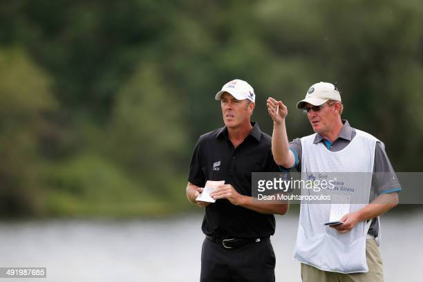 Richard Green of Australia speaks to his caddie before he hits his tee shot on the 12th hole during the final round of the Open de Espana held at PGA...