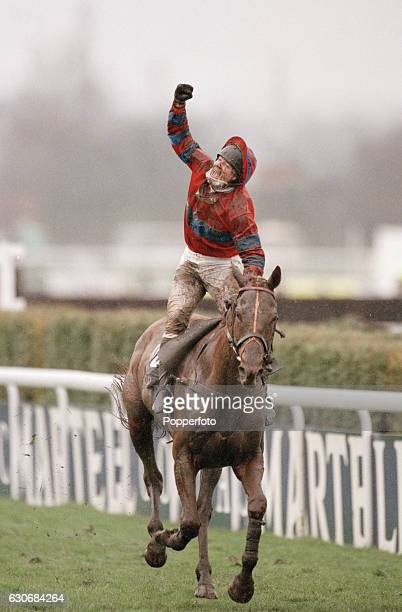Richard Guest riding Red Marauder raises his arm in celebration after winning the Martell Grand National at Aintree, where only four horses finished,...