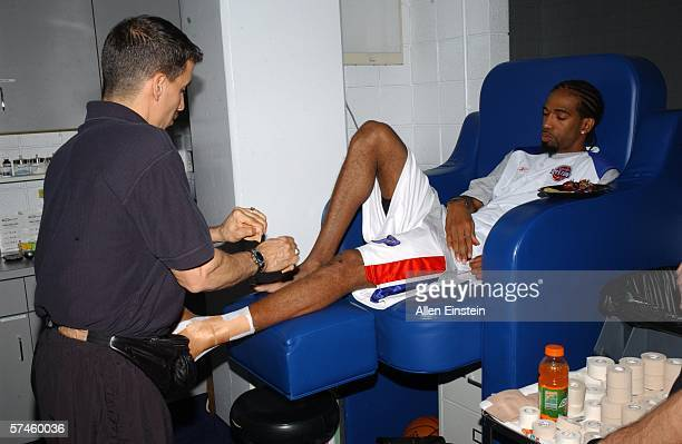 Richard Hamilton of the Detroit Pistons gets his ankles taped by strength and conditioning coach Arnie Kander before taking on the Milwaukee Bucks in...