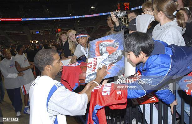 Richard Hamilton of the Detroit Pistons signs a fan's drawing before a game against the Seattle SuperSonics at the Palace of Auburn Hills December...
