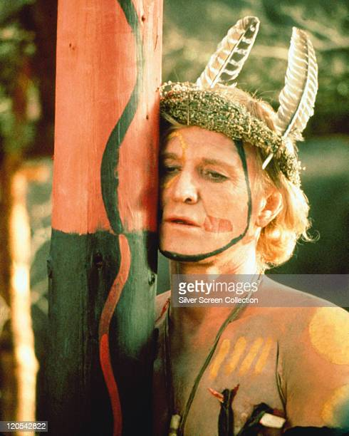 Richard Harris wearing a native American headdress with two feathers and facepaint in a publicity still issued for the film 'A Man Called Horse' 1970...