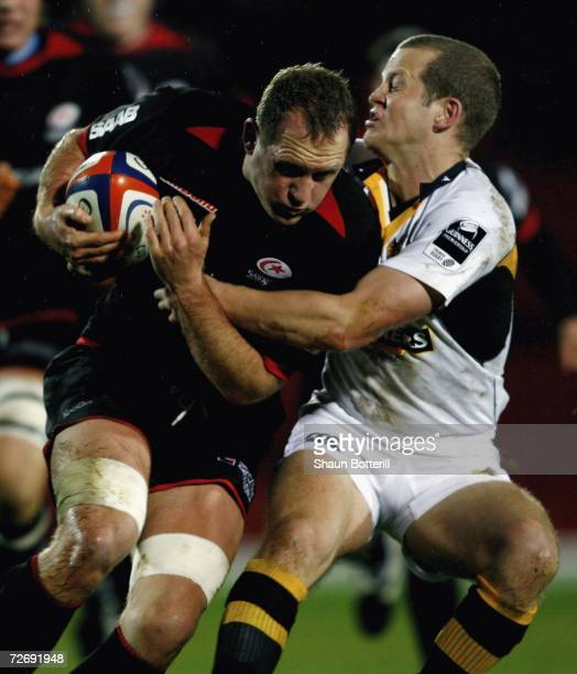 Richard Hill of Saracens is tacxkled by Dave Walder of Wasps during the EDF Energy Cup match between Saracens and London Wasps at Vicarage Road on...