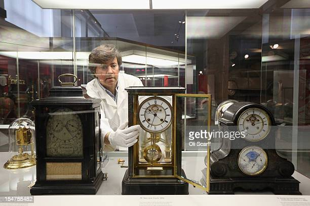 Richard Horton a Conservator at the Science Museum adjusts a French table clock from the 1800s to begin putting clocks back for the end of British...
