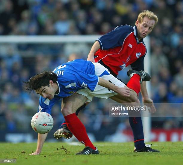 Richard Hughes of Portsmouth is tackled by Ian Kilford of Scunthorpe during the FA Cup Fourth Round match between Portsmouth and Scunthorpe United at...
