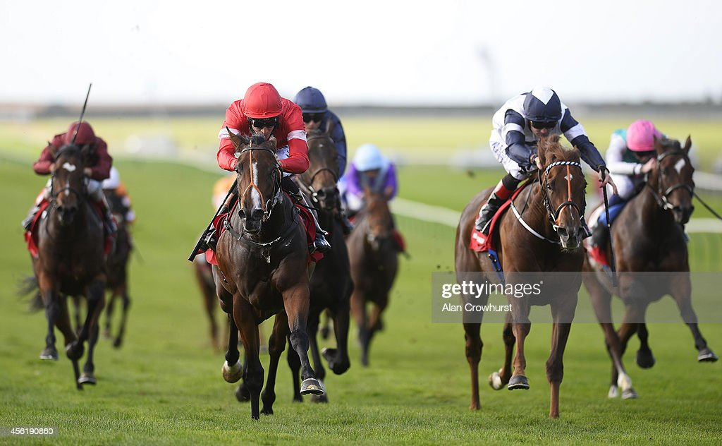 Richard Hughes riding Tiggy Wiggy (red) win The Connolly's Red Mills Cheveley Park Stakes at Newmarket racecourse on September 27, 2014 in Newmarket, England.