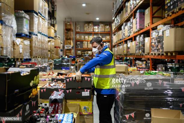 Richard Humphrey, Senior Coordinator for the charity 'His Church', helps prepare pallets of food and supplies which will be distributed to charities...