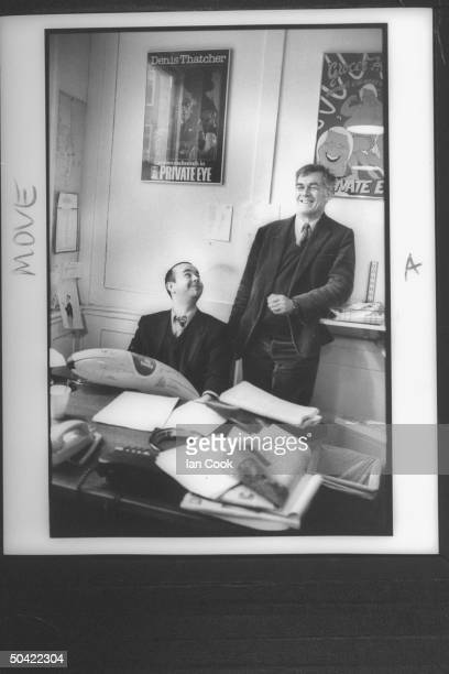 Richard Ingrams founder/exed of the satirical PRIVATE EYE posing w its ed Ian Hislop in editor's room under a Denis Thatcher writes exclusively for...
