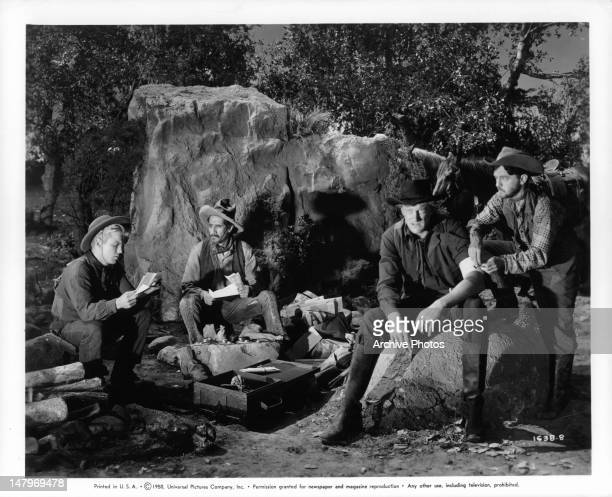 Richard Jaeckel Felipe Turich James Arness and Frankie Darro search their robbery loot for money in a scene from the film 'Wyoming Mail' 1950