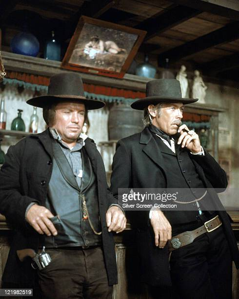 Richard Jaeckel US actor and James Coburn US actor smoking a cigar both wearing black cowboy hats and standing at a bar in a publicity still issued...